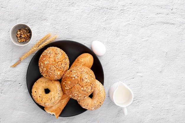Bakery doughnuts and baguette on plate with copy space