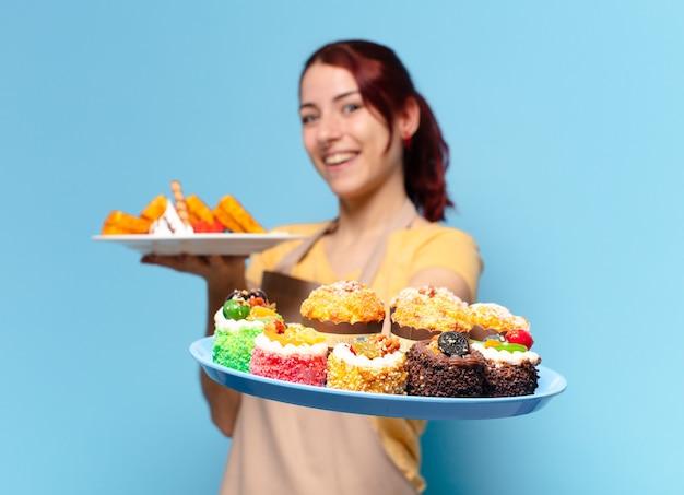 ワッフルとケーキを持つパン屋の従業員の女性