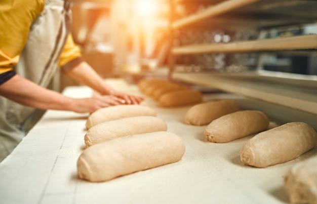 베이커리 식품 공장, 신선한 식품 생산. 제빵사는 작업대에 앉아 빵을 만듭니다.
