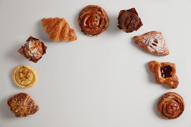 Set di prodotti alimentari da forno. grande varietà di deliziosi dolci a semicerchio su sfondo bianco. croissant, muffin, turbinii e panini da mangiare. buonissimo dessert. cibo dolce e alimentazione malsana