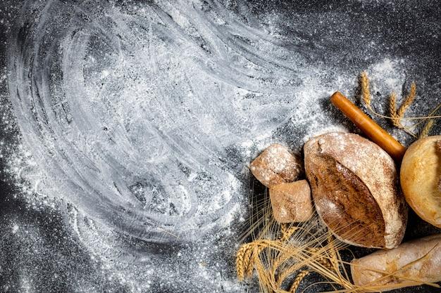 빵집. 어두운 배경에 밀 귀가 있는 갓 구운 바삭한 빵과 빵, 복사 공간 위쪽 전망