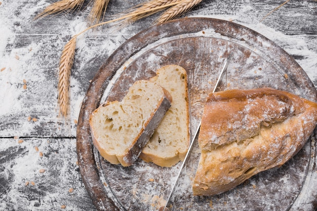 Bakery and grocery concept. fresh, healthy white bread loaf, sprinkled flour, wheat ears on rustic table and wooden round board, food top view
