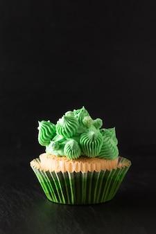 Bakery  homemade sponge vanilla cupcake green tone buttercream on black