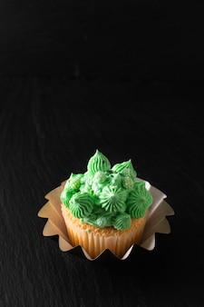 Bakery  homemade sponge vanilla cupcake green tone buttercream on black