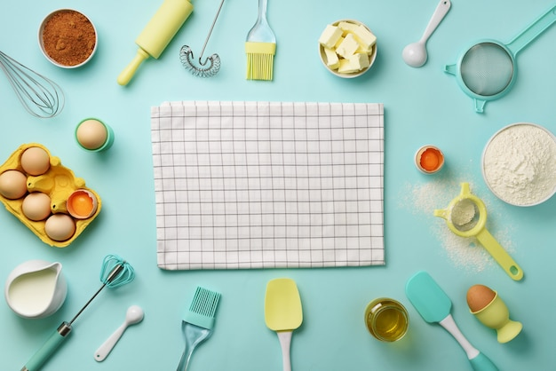 Bakery ingredients over blue background - butter, sugar, flour, eggs, oil, spoon, rolling pin, brush, whisk, towel.