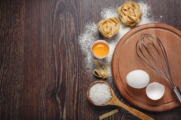 Bakery ingredients. flour with raw eggs for dough pasta on a wooden background