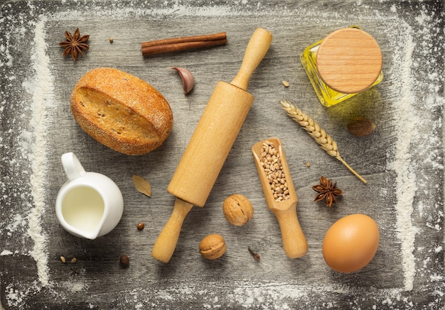Bakery ingredients on wooden background, top view