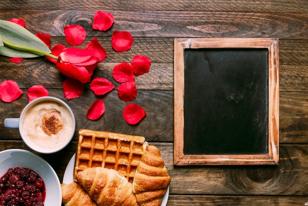 Bakery on plate near cup of drink, flower, jam, petals and photo frame