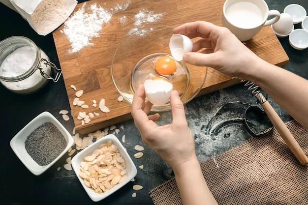 베이커리 과정. 건강한 베이킹 재료 - 밀가루, 아몬드 견과류, 계란, 검은 배경에 우유. 평면도, 평면도. 현대 요리 구성입니다. 주방 용품.