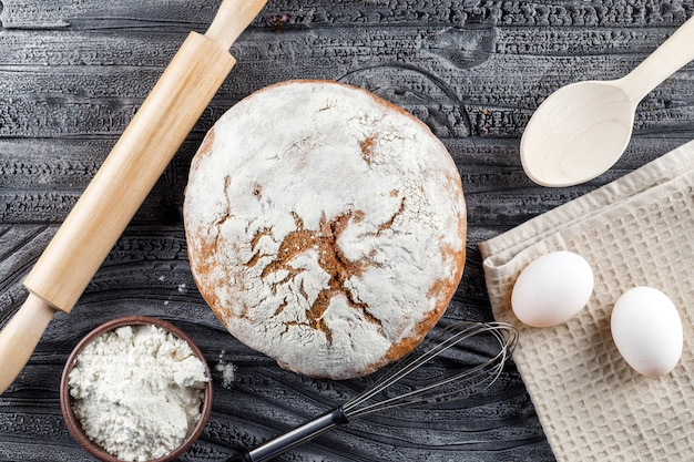 Bakery product with rolling pin, flour, eggs top view on a gray wooden surface