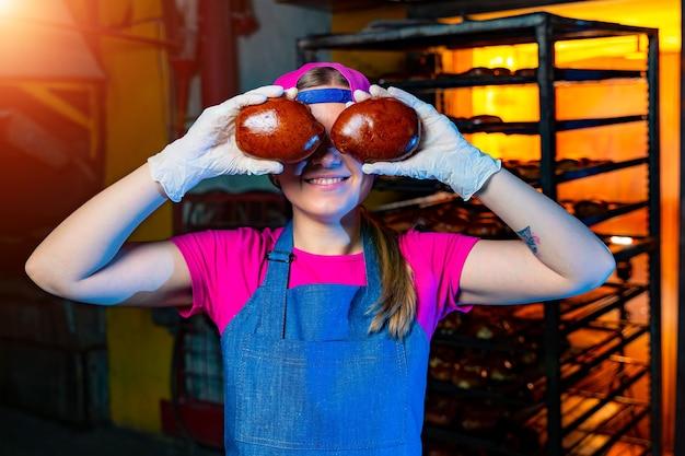 Производство хлебобулочных изделий. заводская печь фон. булочки и свежие пироги. руки держат две булочки возле глаз.