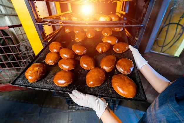 ベーカリー生産。工場オーブンの背景。トレイのパンと新鮮なパイ。
