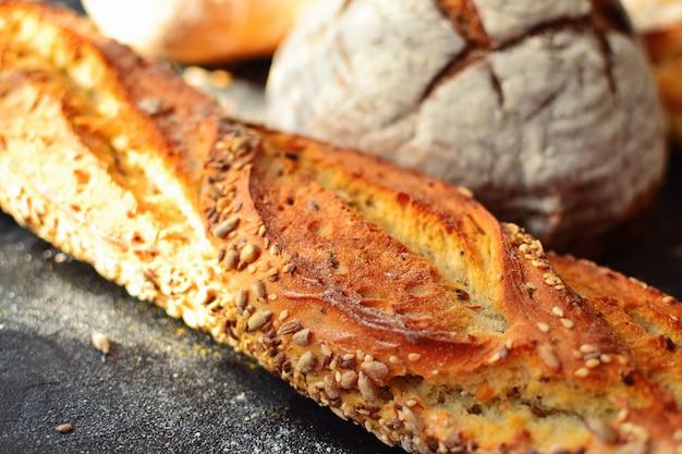 Хлебобулочные изделия в плетеной корзине. круглый домашний хлеб, батон с семенами, веганский хлеб без дрожжей