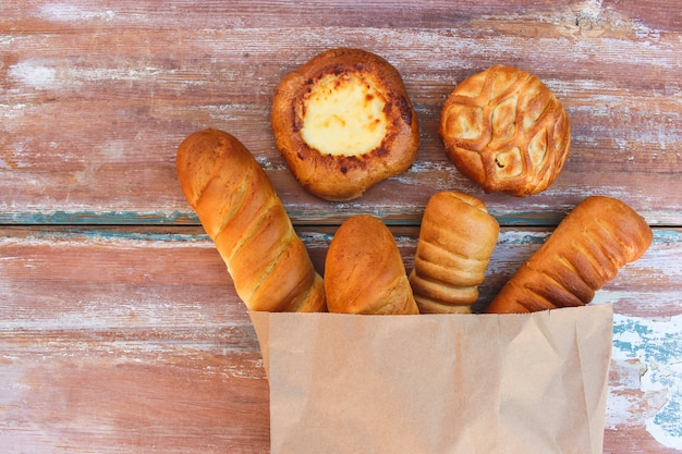 Bakery products in paper bag on table in top view