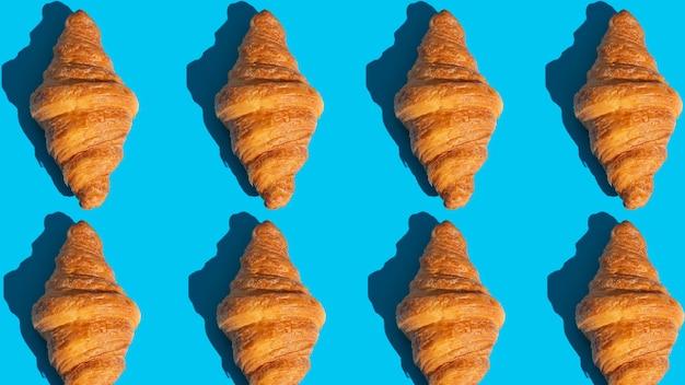 焼きクロワッサンを使ったベーカリー製品のパターン。青い背景、上面図。ポップアートスタイル。美味しくて食べ物のコンセプト。