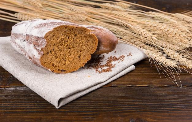 Буханка ржаного хлеба, разрезанная пополам поверх коричневой ткани, рядом с семенами и сушеными стеблями пшеницы над деревянным столом