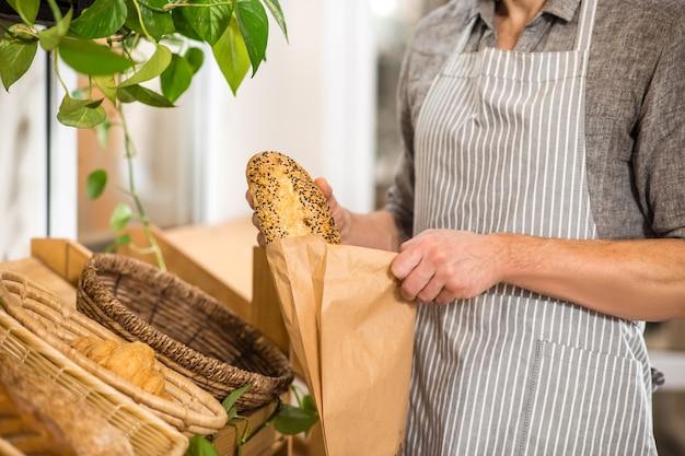 Булочная. мужские руки кладут свежий аппетитный хлеб в бумажную упаковку в мини-пекарне