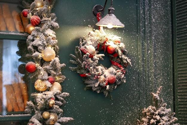 Витрина пекарни украсила рождественский еловый венок с красной лентой и шарами. декор зимнего кафе