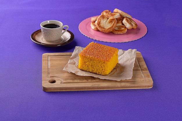 당근 케이크와 프랑스 빵을 배경으로 컵 o 옆에 있는 나무 판자에 있는 베이커리 과자