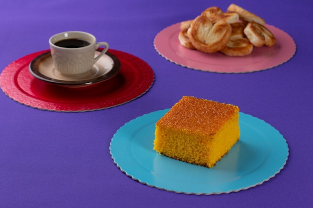 Bakery sweets on a wooden board with a carrot cake and french bread in the background beside a cup o