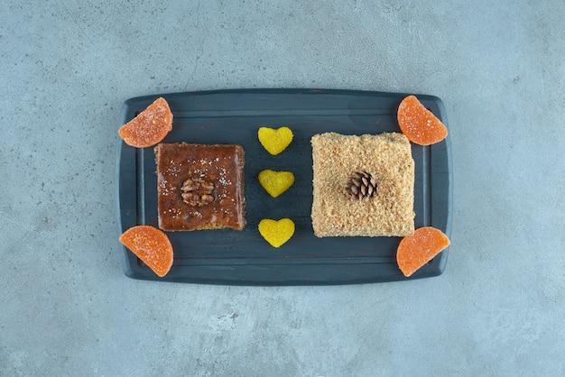 Бахлава, кусок торта и несколько желейных конфет на темно-синем фоне на мраморной поверхности