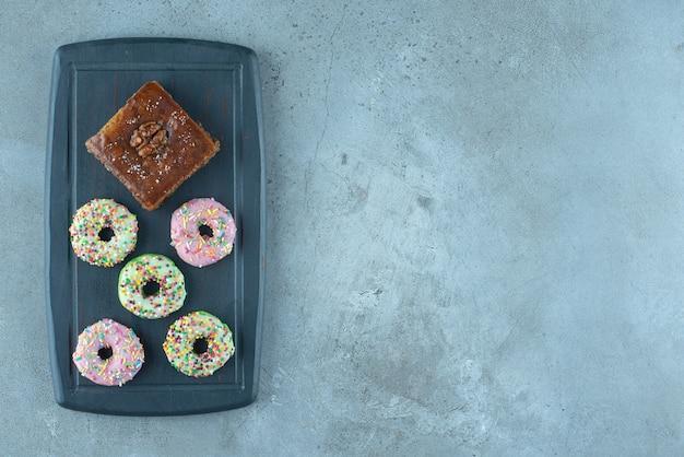 Бахлава и пончики на синей доске на мраморной поверхности