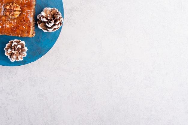 Бахлава и две сосновые шишки на синей доске на мраморной поверхности