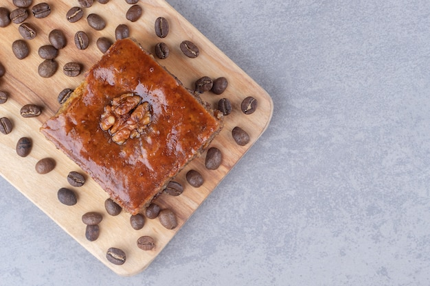 Bakhlava and coffee beans on a wooden board on marble table.