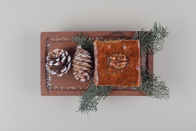 작은 쟁반에 bakhlava는 소나무 콘과 대리석 배경에 나뭇잎으로 장식되어 있습니다.