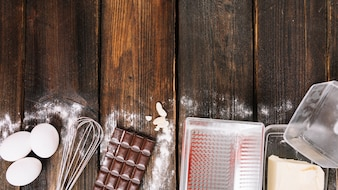 Baking a cake ingredients with kitchen utensil on wooden plank