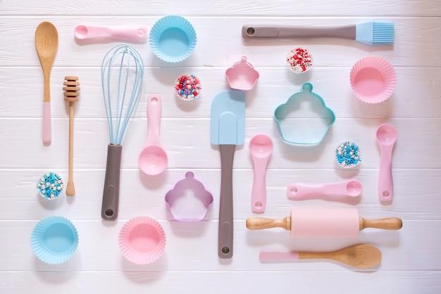 ベーキングおよび調理の概念。お菓子を作るためのクッキーカッター、泡立て器、ローラーピン、キッチンベークツールで作られたパターン。白色の背景。静物を焼く休日のトップビュー