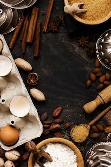오래 된 어두운 나무에 밀가루, 설탕, 향신료, 견과류, 계피, 나무 숟가락 및 롤링 핀으로 베이킹 및 요리 프리미엄 사진