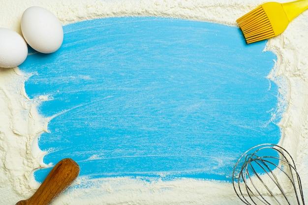 Выпечка и тесто на фоне пшеничной муки и кухонных принадлежностей на синем кухонном столе.