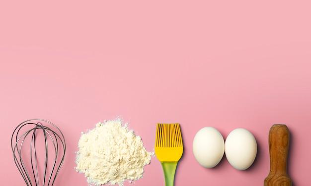 Фон для выпечки и теста пшеничная мука и кухонные принадлежности на розовом кухонном столе.