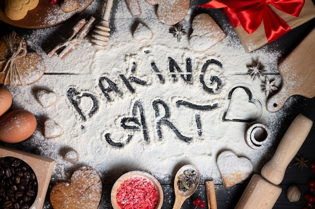 Baking art written on flour. gingerbread heart shaped cookies, spices, coffee beans and baking supplies on black wood background
