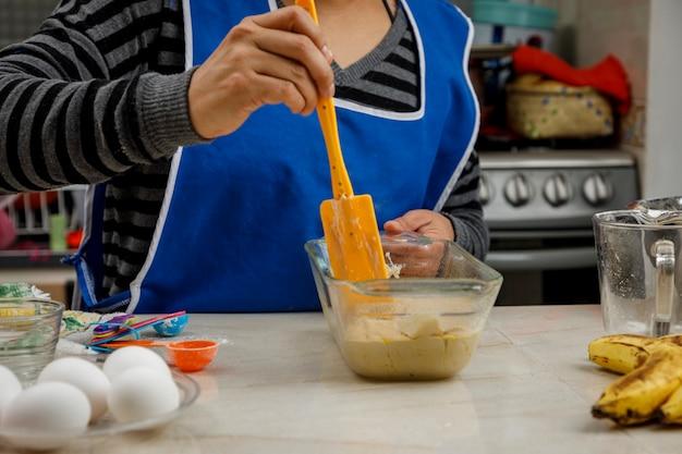 Выпечка дома женщина готовит банановый блин на кухне