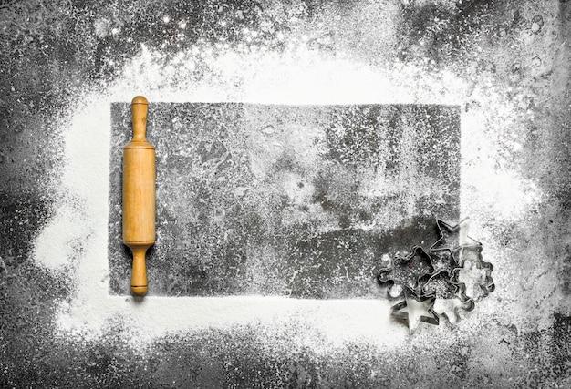 Фон выпечки. рамка из муки и инструменты для теста. на деревенском фоне.