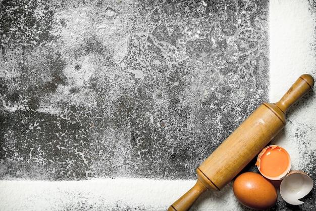 Фон выпечки. рамка из муки со скалкой и свежими яйцами. на деревенском фоне.