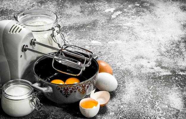 Фон выпечки. взбить яйца миксером, чтобы получилось тесто. на деревенском фоне.