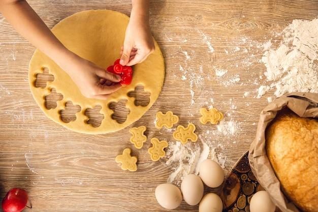 Фон выпечки: ребенок делает печенье. крупным планом, вид сверху