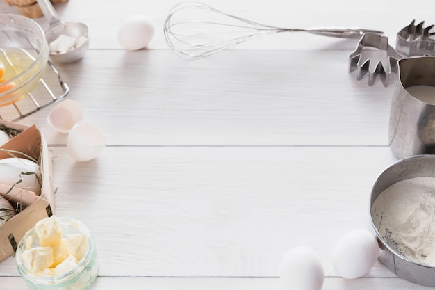 Baking background. cooking ingredients for dough and pastry, eggs yolks, flour on white rustic wood.