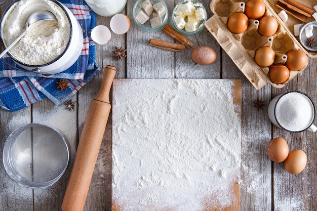 Baking background. cooking ingredients for dough and pastry making and sprinkled with flour board on rustic wood. top view