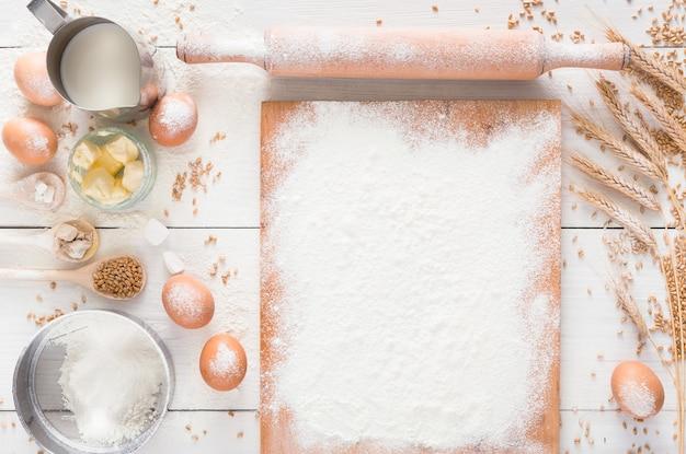 Фон выпечки. приготовление ингредиентов для дрожжевого теста, яиц, муки и молока на белом деревенском дереве. вид сверху