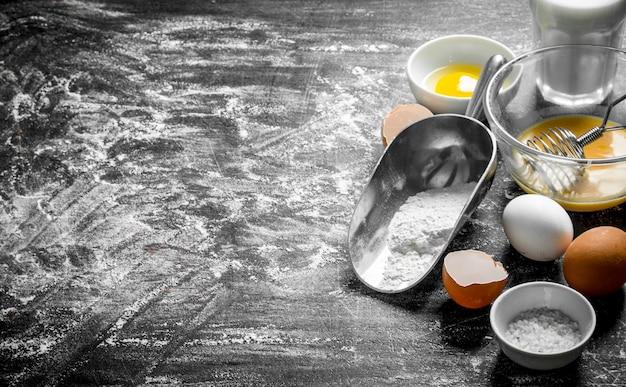 Фон выпечки. мука с яйцом и молоком. на деревенском фоне