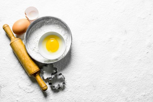 Фон выпечки. мука с яйцом, скалкой и формами для теста.