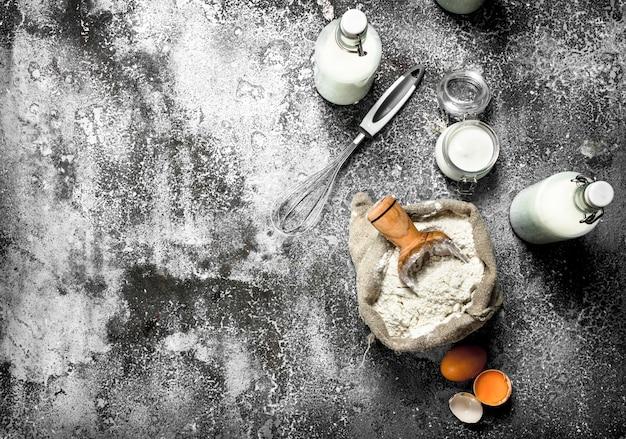 ベーキングの背景。新鮮な牛乳を瓶に入れ、サワークリームと卵を入れて小麦粉をまぶします。素朴な背景に。