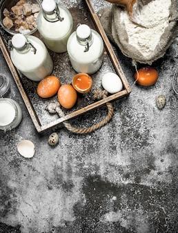 Фон выпечки. мука со свежим молоком в бутылках, сметана и яйца. на деревенском фоне.