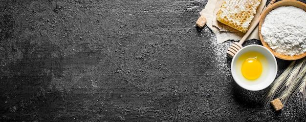 ベーキングの背景。ボウルに蜂蜜と卵を入れて小麦粉をまぶします。黒の素朴な背景に