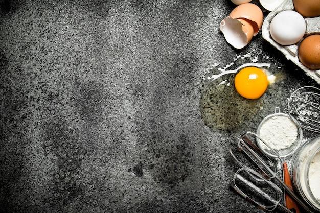 ベーキングの背景素朴な背景に散らばった小麦粉から新鮮な卵
