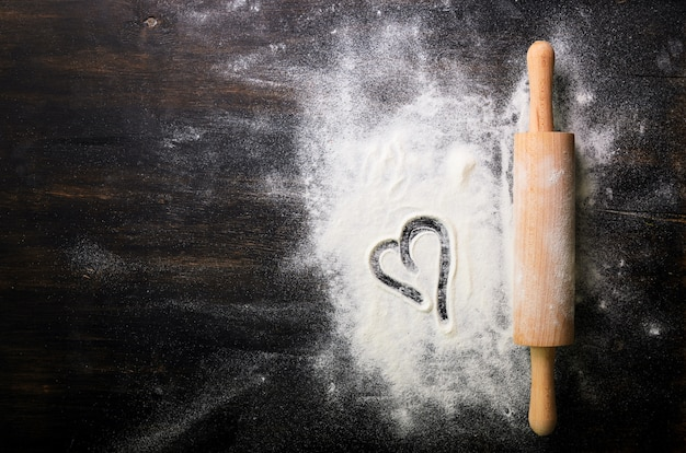 Baking background. heart of flour and rolling pin on dark table with copy space, top view.